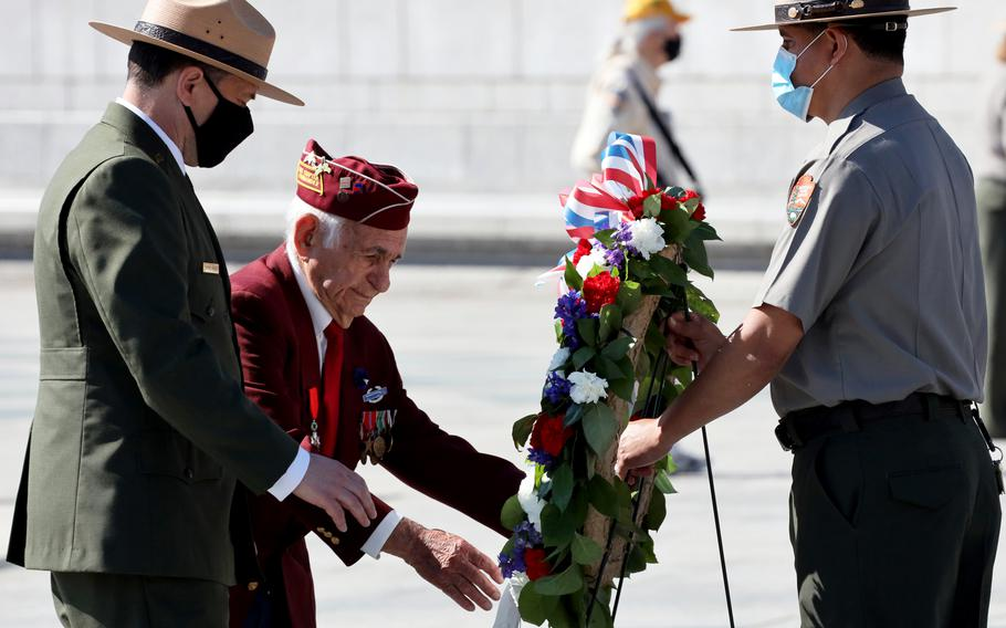 World War II veteran Harold Radish, center, and Superintendent of the National Mall and Memorial Parks Jeffrey Reinbold place a wreath during a Memorial Day ceremony at the National World War II Memorial in Washington, D.C., May 31, 2021.