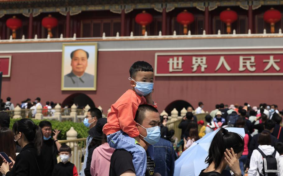 A man and child wearing masks visit Tiananmen Gate near the portrait of Mao Zedong in Beijing on May 3, 2021.