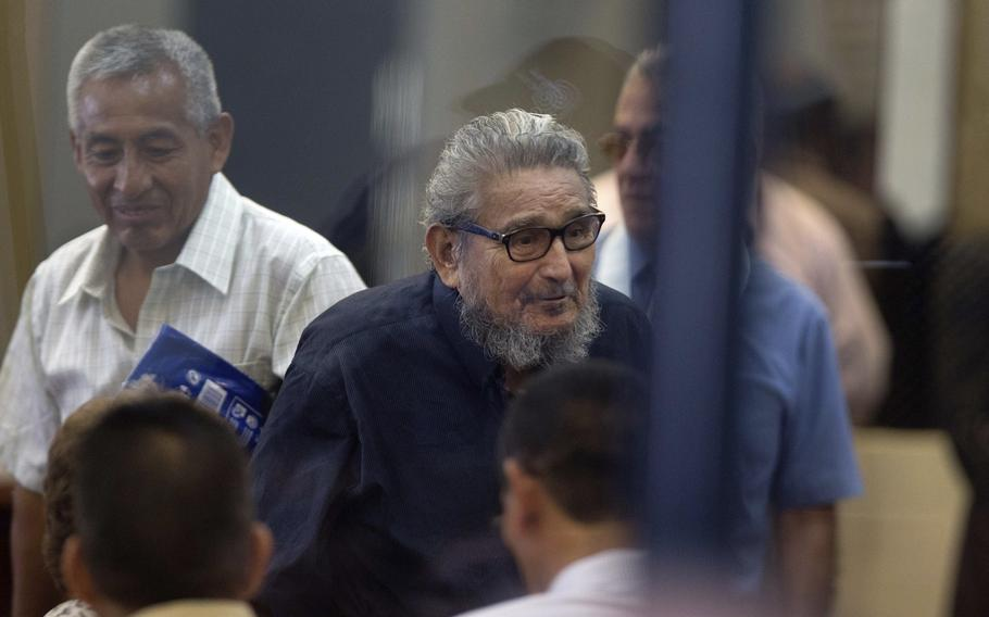 Abimael Guzmán, founder and leader of the Shining Path guerrilla movement, center, enters a courtroom at the Naval Base in Callao, Peru, on Feb. 28, 2017.