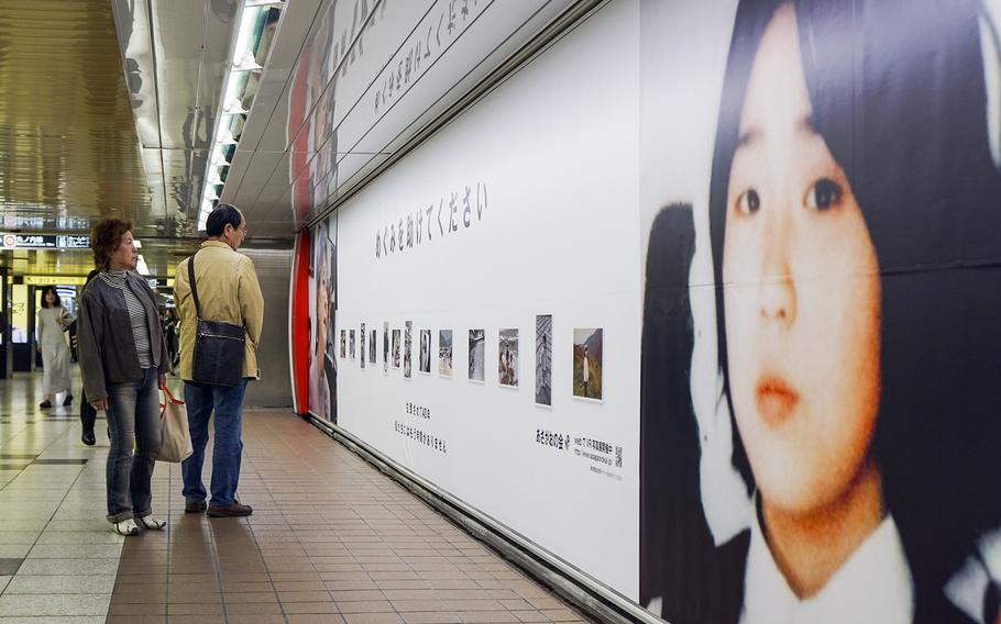 Commuters look at photos of Megumi Yokota, who was abducted by North Koreans in 1977, displayed at Shinjuku Station in Tokyo, May 9, 2018.