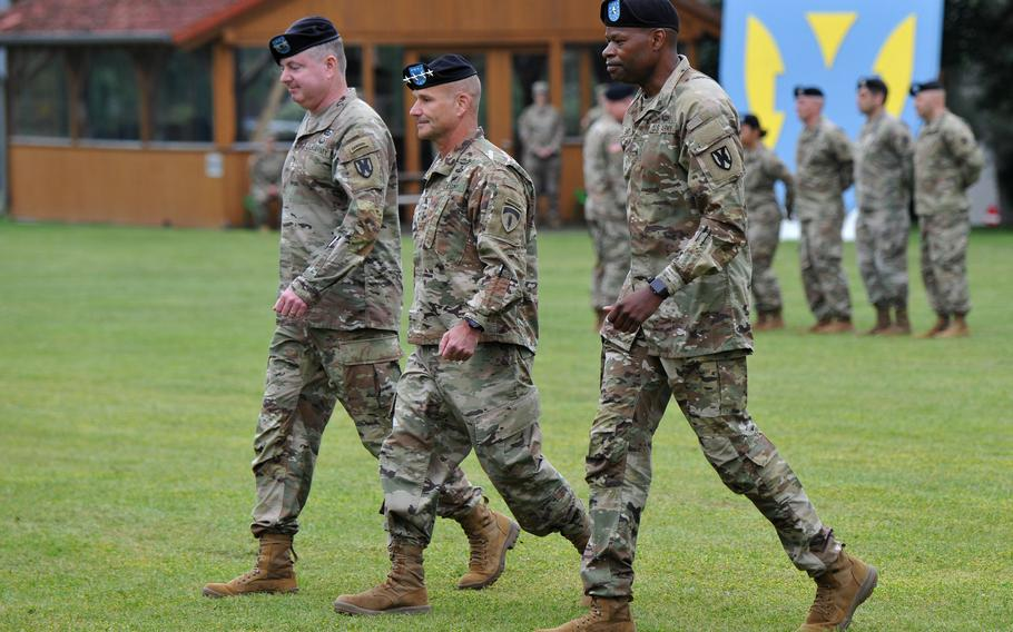 Outgoing commander of the 21st Theater Sustainment Command, Maj. Gen. Christopher Mohan, left, and the incoming commander, Brig. Gen. James Smith, flank U.S. Army Europe and Africa commander Gen. Christopher Cavoli as they march off the field at Daenner Kaserne in Kaiserslautern, Germany, June 8, 2021.