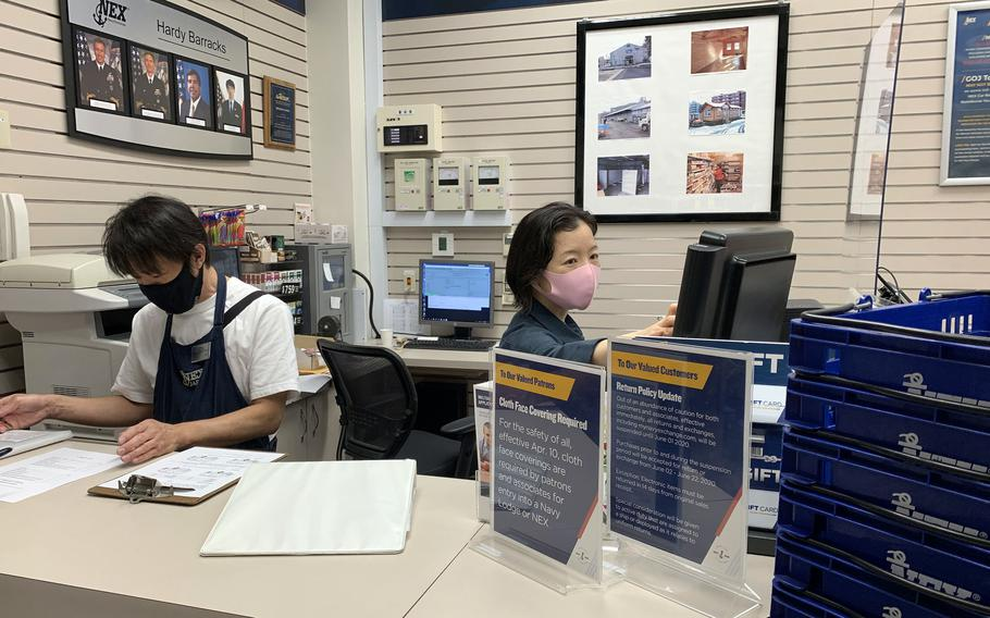 Navy Exchange employees wear masks while working inside a shop at Hardy Barracks in central Tokyo, Friday, May 28, 2021.