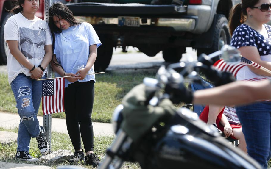 Nancy Martin, left, and her sister Maribel Martin, right, watch motorcycles pass during the funeral procession for Marine Corps Cpl. Humberto Sanchez on Sunday, Sept. 12, 2021, in Logansport, Ind.