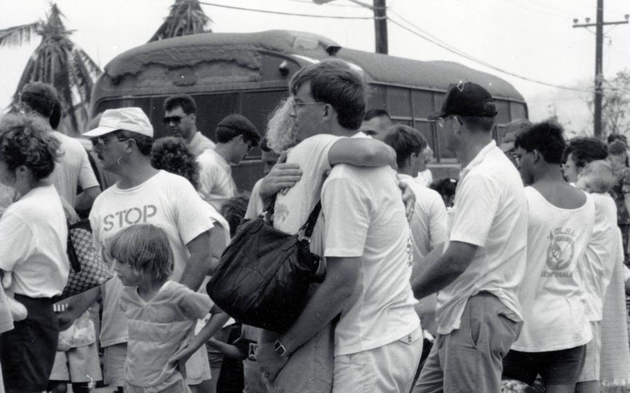 Mark Hanneman hugs his wife, Susan, shortly before she and their daughter Sarah, left, were evacuated from Naval Station Subic Bay due to the eruption of Mount Pinatubo in the Philippines, in June 1991.