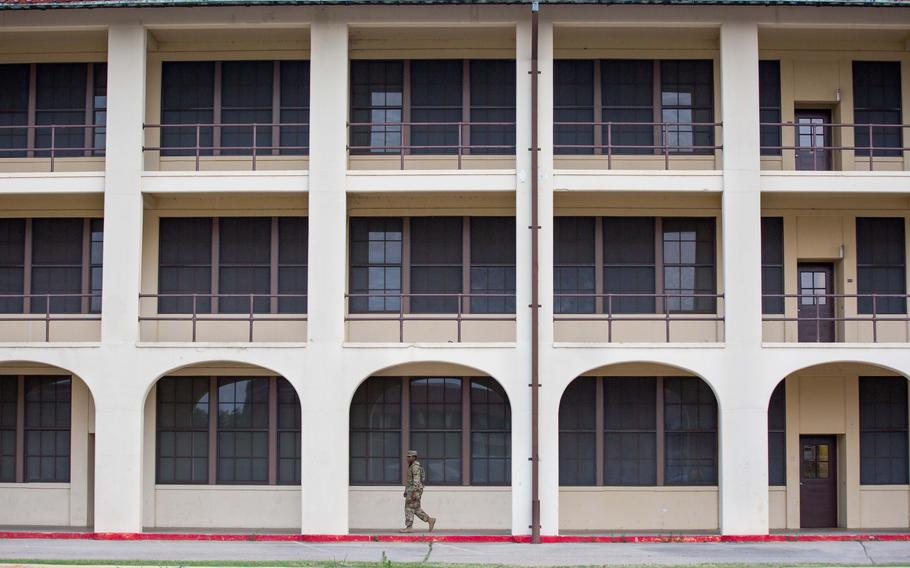 A soldier walks through the barracks at Fort Benning, Ga., where Pvt. Felix Hall lived before his death in 1941.