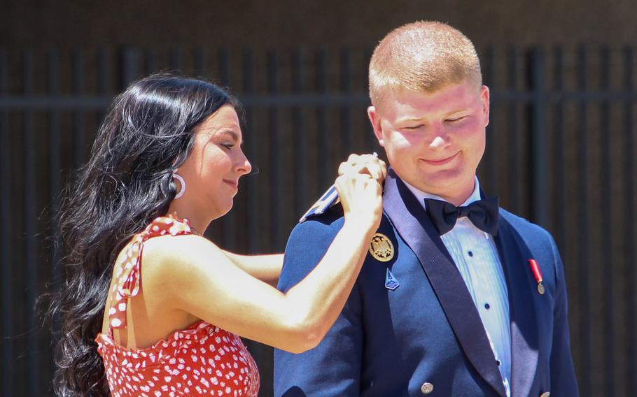 Tanner Johnson's fiancee, Brynn Woodyard, pins on his second lieutenant bars at the commissioning ceremony for Cadet Squadron 14 at the U.S. Air Force Academy in Colorado Springs, Colo., May 25, 2021. Johnson was the first person diagnosed with Type 1 diabetes to commission into the U.S. military.