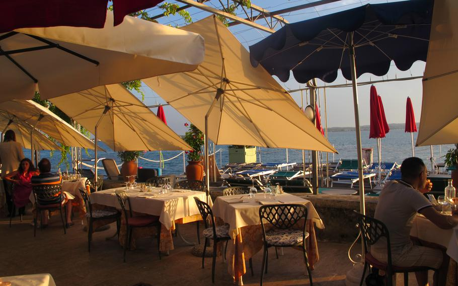 The Catullo Hotel in Sirmione, Italy serves dinners on a covered patio near Lake Garda, where the sun still shines at 7 p.m. in summer.