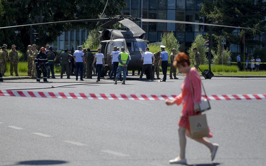 Servicemen walk by a U.S military Black Hawk helicopter following an emergency landing on a busy boulevard in Bucharest, Romania, Thursday, July 15, 2021. A U.S military Black Hawk helicopter that took part in preparations for Romanian Aviation day, which is set to take place on July 20, was forced to land on a busy Bucharest boulevard Thursday morning, damaging two cars after knocking down two lampposts. No casualties were reported.