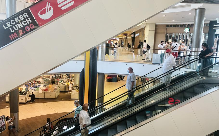 Shoppers ride the escalators in the K in Lautern mall in Kaiserslautern, Germany. Under new rules in the state of Rheinland-Pfalz, shops and restaurants will no longer have to shut down when coronavirus numbers tick up above certain levels.