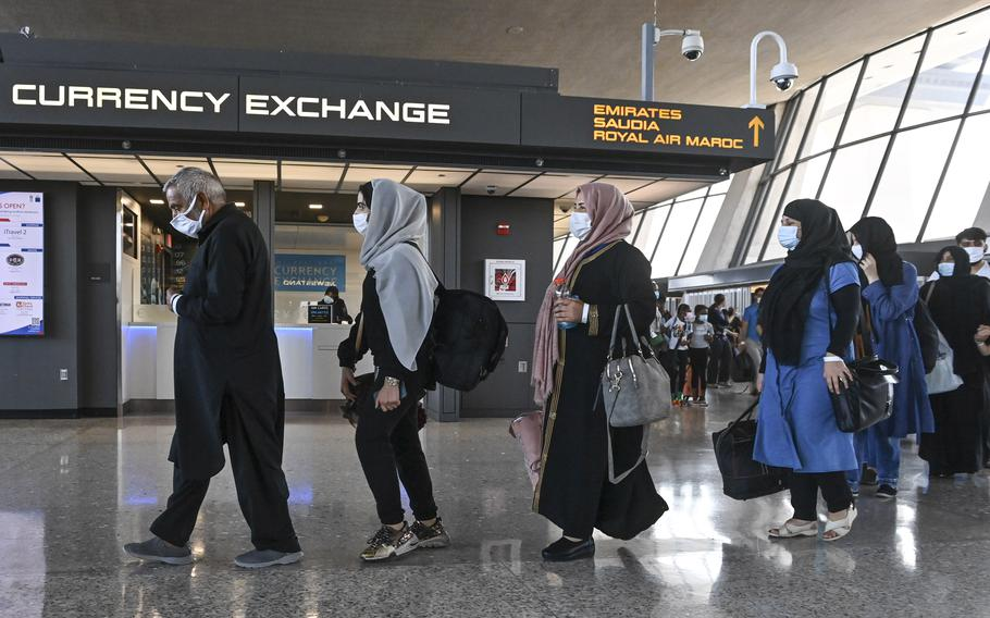Refugees who fled Afghanistan walk through the terminal to board a bus after arriving at Dulles International Airport on Aug. 27, 2021, in Chantilly, Va.