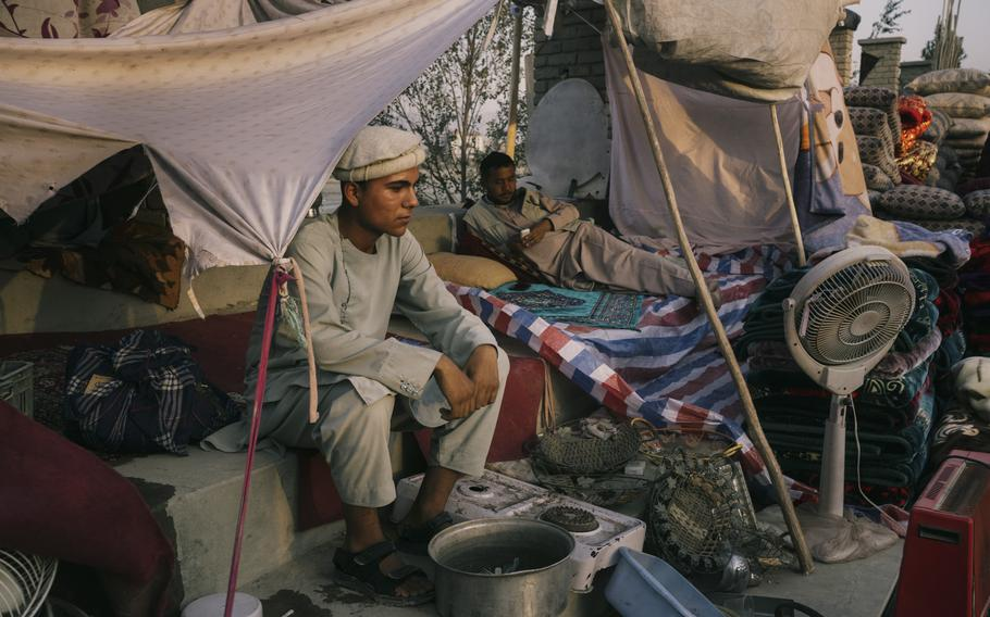 A family waits for buyers on Sept. 29, 2021, in a sprawling market that has appeared in Kabul near Ghazi Stadium.