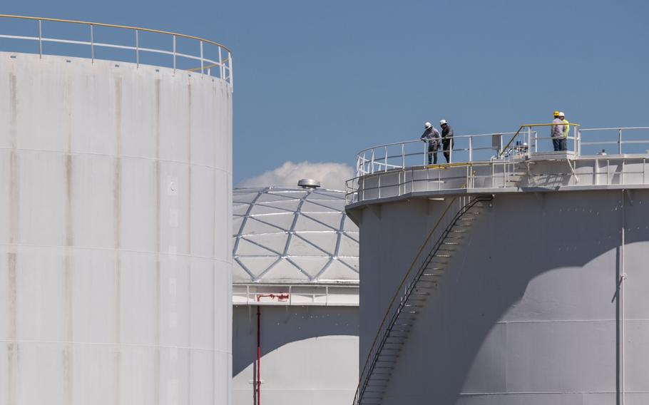 Workers stand on top of a tank at a Colonial Pipeline Inc. facility in Avenel, N.J., on May 12, 2021.