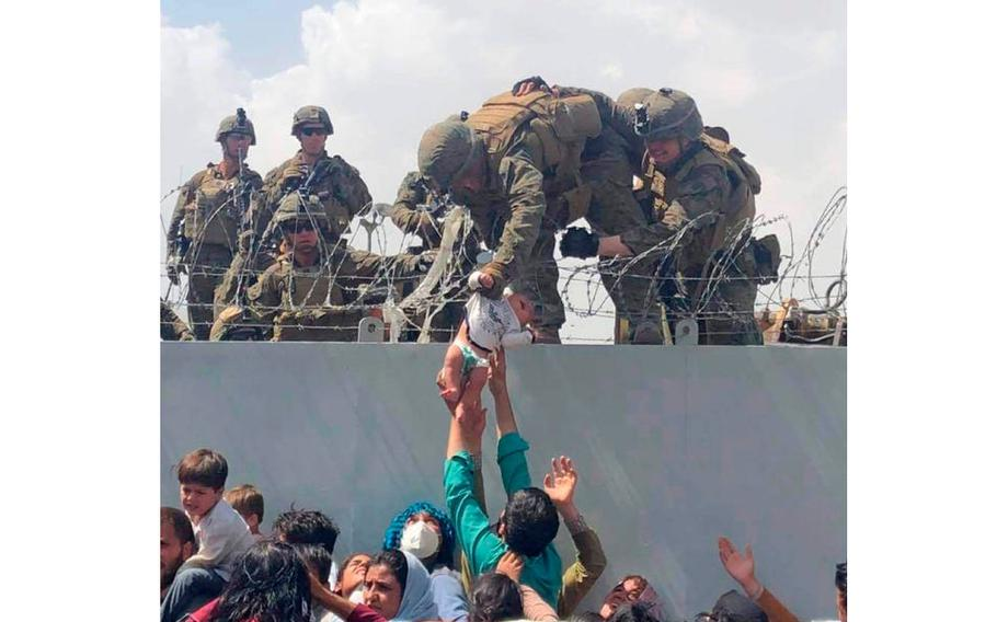 A Marine pulls a baby over the wall at the Kabul airport on Aug. 19, 2021.