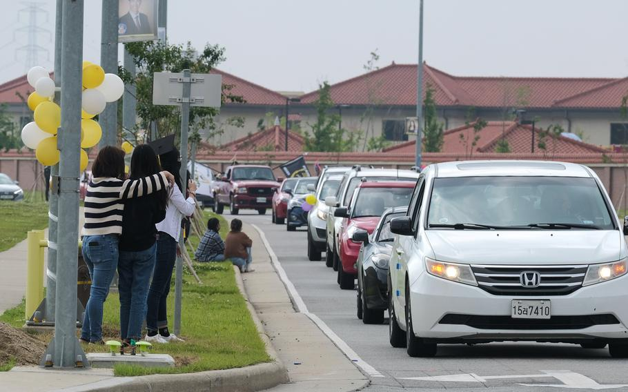 Carfuls of people take part in a reverse parade to congratulate graduating high school seniors lining the streets at Camp Humphreys, South Korea, Thursday, May 27, 2021.