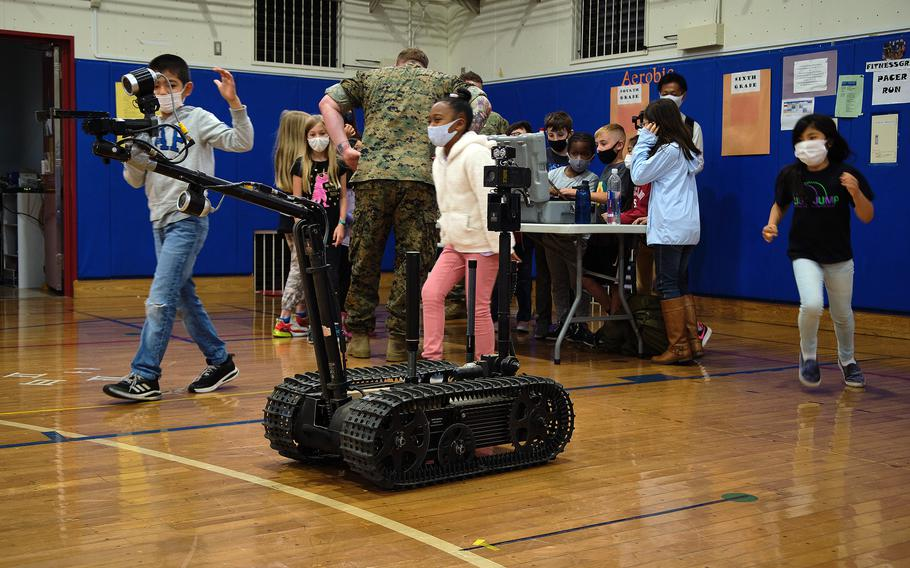Lanham Elementary School students observe and control a robot used by a Marine Corps explosive ordnance teams during a STEAM event at Naval Air Facility Atsugi, Japan, May 27, 2021.