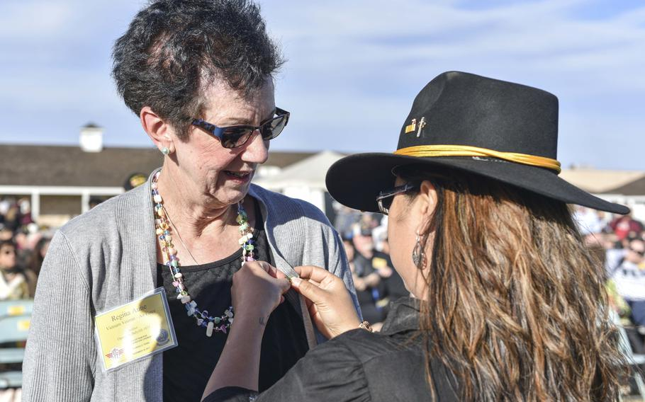 """U.S. Air Force retired Col. Regina Aune receives a Vietnam veteran lapel pin from Aryn Lockhart, 17th Training Wing Public Affairs visual information specialist, during the 50th Vietnam War Commemoration at the Fort Concho parade ground in San Angelo, Texas, Nov. 18, 2017. Lockhart was one of the babies from Operation Babylift who survived a plane crash and was adopted and raised in Northern Virginia. In 1997, not long after graduating from Virginia Tech, she began investigating her life story, hoping to write about it. She typed """"Operation Babylift"""" into the nascent Internet and found an article recounting Aune's heroism, which had resulted in her receiving the prestigious Cheney Award for valor from the Air Force."""