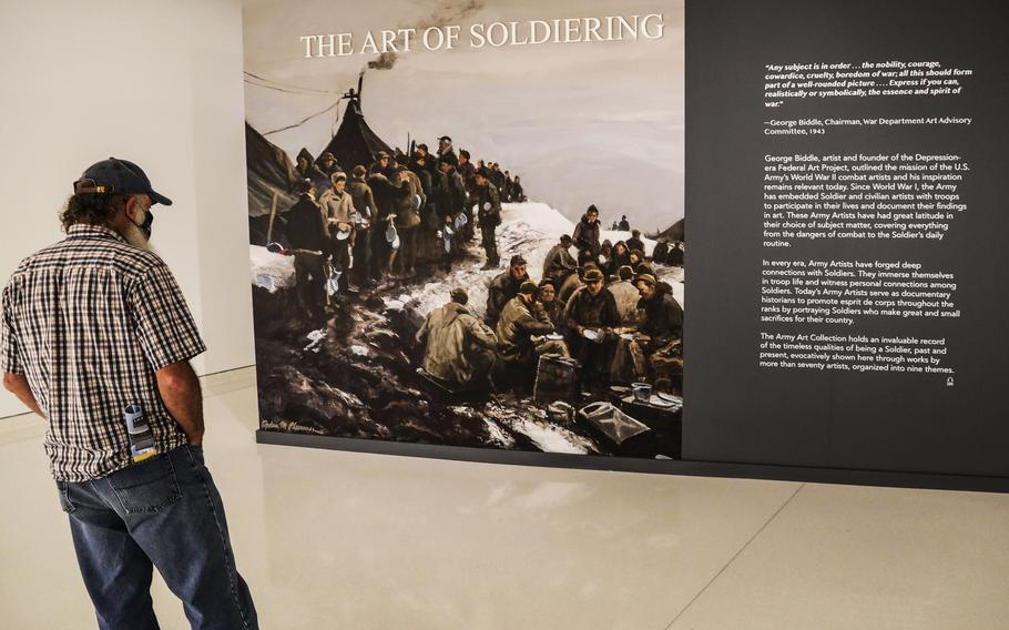 A visitor reads the introduction to the Art of Soldiering exhibit at the National Museum of the United States Army on its reopening day, June 14, 2021.
