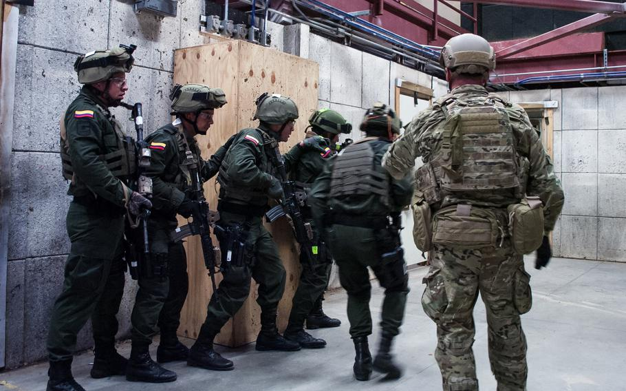A U.S. Special Forces soldier observes elite Colombian troops during training at Eglin Air Force Base in Florida in 2015. The two militaries have a partnership dating back decades.