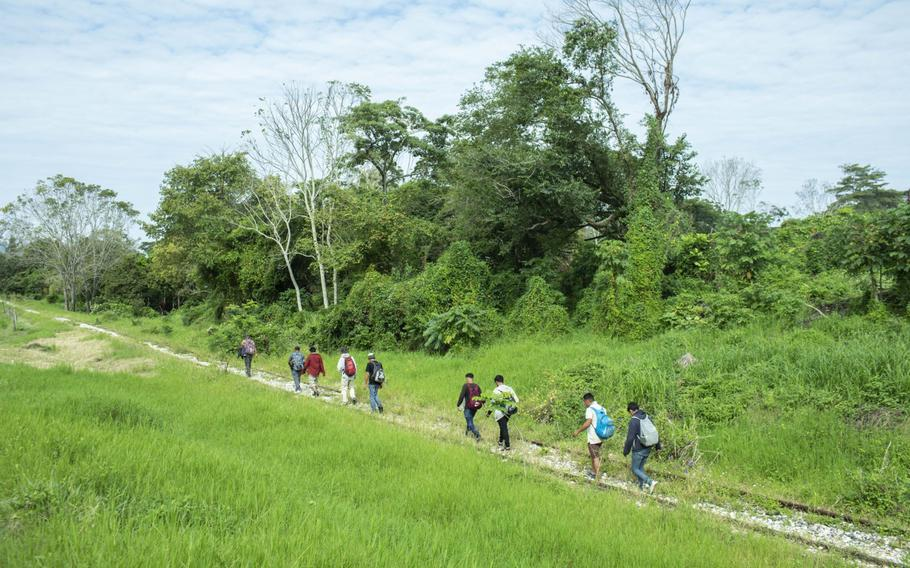 Migrants from Honduras walk along a railway track in Tenosique, Mexico, on March 8, 2021.