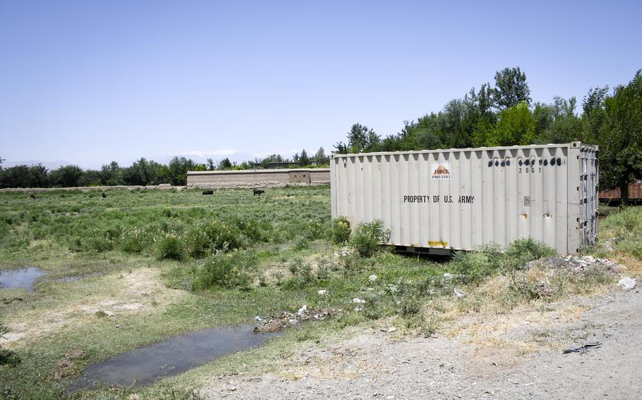 A shipping container that belonged to the U.S. Army sits in a field near cows at a farm outside of Bagram Airfield, Afghanistan. A surge of containers and junk have been trucked out of Bagram since May, residents near the base said June 5, 2021.