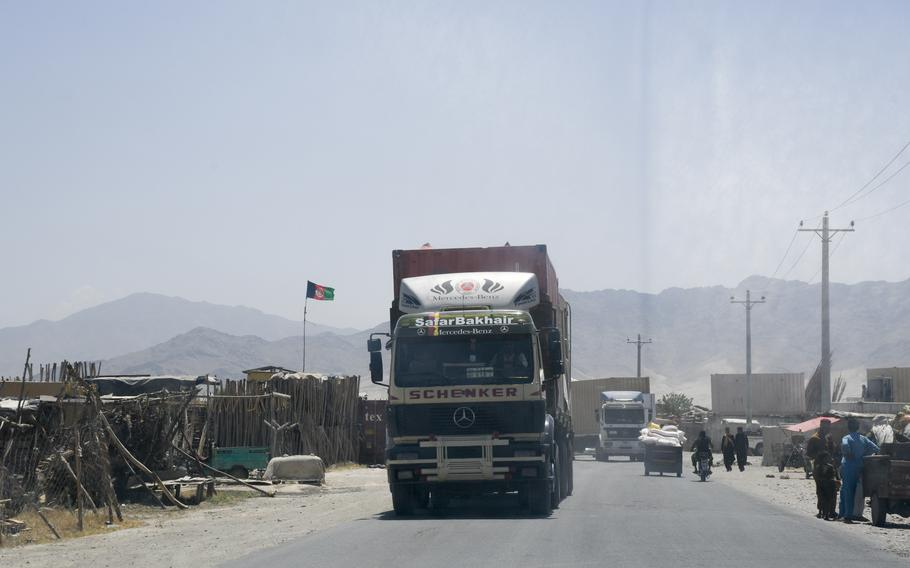 A line of trucks drives out a gate at Bagram Airfield, Afghanistan on June 5, 2021. A surge of containers and junk have been trucked out of Bagram since May, residents near the base said.