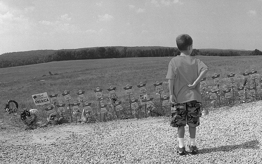 A child looks at angel figures, Aug. 4, 2002,  placed at the edge of the field near Shanksville, Pa. where United Flight 93 crashed on Sept. 11, 2001. Forty-four people died, including the hijackers.