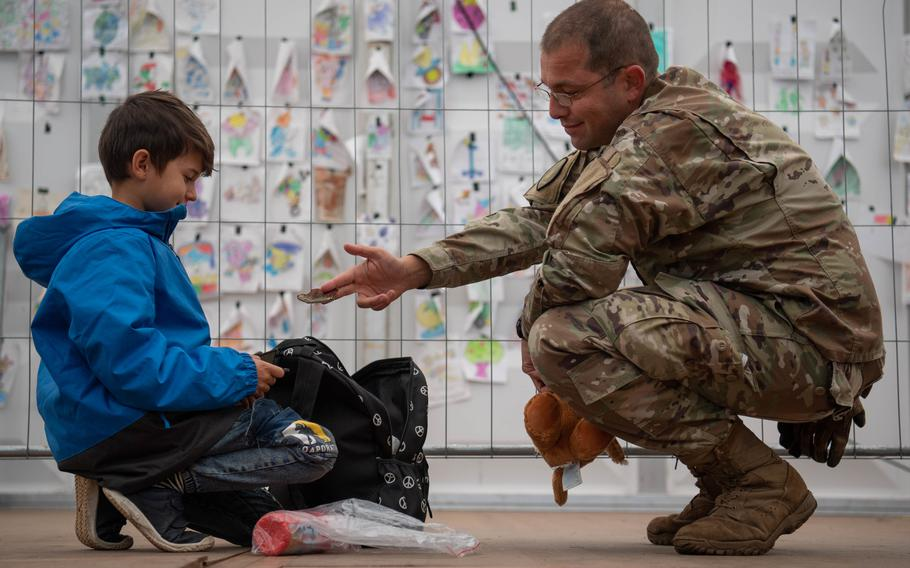 U.S. Air Force Tech. Sgt. Manuel Villarreal, 691st Cyber Operations Squadron virtual operations supervisor, offers his patch to an evacuee at Ramstein Air Base, Germany, Saturday, Oct. 9, 2021. Around 300 Afghans left Ramstein that day when flights for evacuees to the U.S. resumed after a three-week pause.