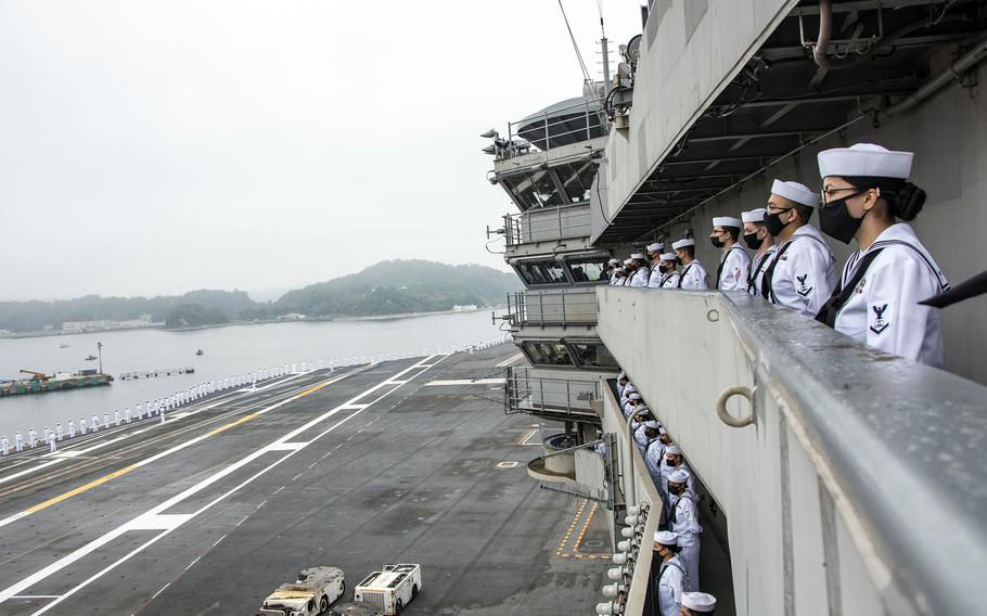 Sailors man the rails aboard the aircraft carrier USS Ronald Reagan as it departs Yokosuka Naval Base, Japan, Wednesday, May 19, 2021.