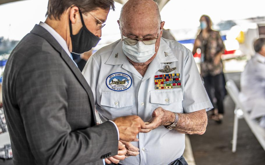 Defense Secretary Mark T. Esper presents World War II Veteran Jack DeTour with a coin at the luncheon during the 75th Anniversary of the End of World War II commemoration ceremony held aboard the Battleship Missouri Memorial, Sept. 2, 2020.