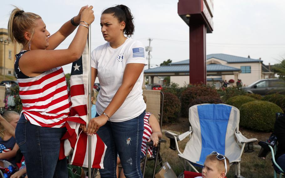 Emma Logan, left, and her twin sister Elly Logan, right, set up an American flag before the funeral procession for Marine Corps Cpl. Humberto Sanchez on Sunday, Sept. 12, 2021, in Logansport, Ind.