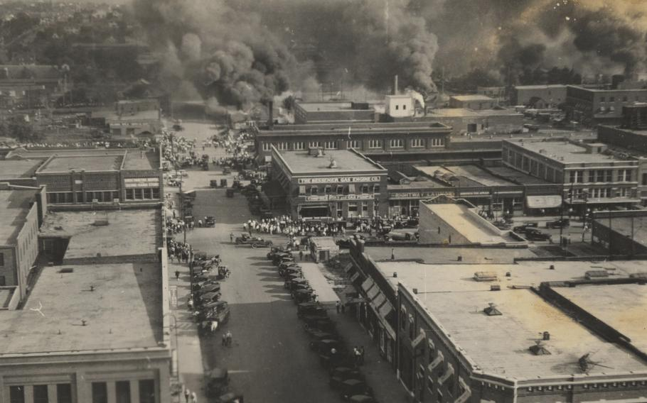 This photo provided by Department of Special Collections, McFarlin Library, The University of Tulsa shows crowds of people watching fires during the June 1, 1921, Tulsa Race Massacre in Tulsa, Okla.
