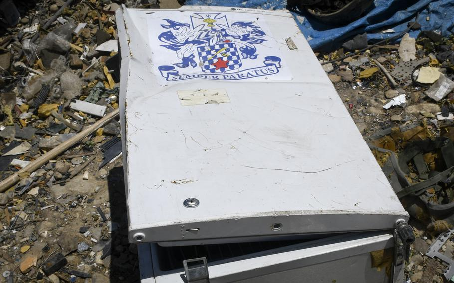 A small fridge containing the coat of arms of the U.S. Armys 16th Infantry Regiment, and the Latin motto, Semper Paratus, meaning Always Ready, lies slightly crushed at a trash yard outside Bagram Airfield, Afghanistan June 5, 2021.