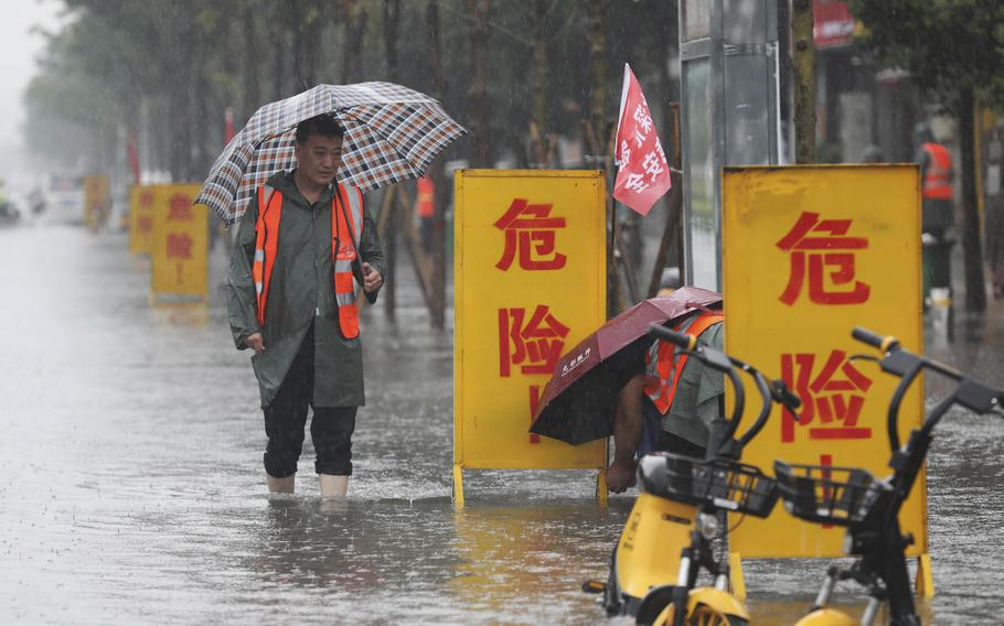 """Staff members set up warning signs with the words """"Danger!"""" at a waterlogged area in Wuzhi County in central China's Henan Province on Tuesday."""