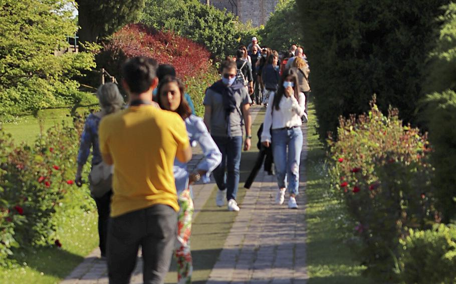 Visitors walk along a path with a view of the Scaligero Castle in Villafranca di Verona, from the Avenue of the Roses, inside the Garden Park Sigurta.