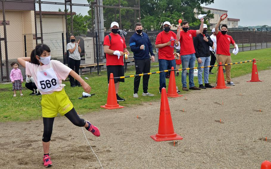 Volunteers cheer on a competitor in the Kanto Plains Special Olympics at Yokota Air Base, Japan, Saturday, May 22, 2021.