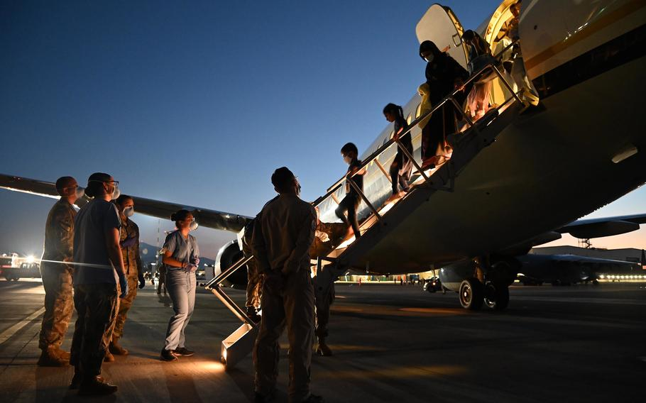 U.S. service members assist evacuees from Afghanistan as they depart a U.S. Navy Boeing C-17A Clipper at Naval Air Station Sigonella, Italy, Aug. 28, 2021.