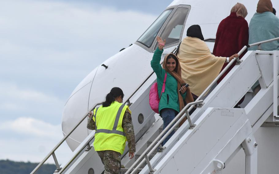 An Afghan evacuee boards a commercial flight at Ramstein Air Base, Germany, on Aug. 26, 2021. Flights carrying Afghans to the U.S. are still on hold three days after it was announced that flights would be halted because of measles infections among evacuees who recently arrived in the United States.
