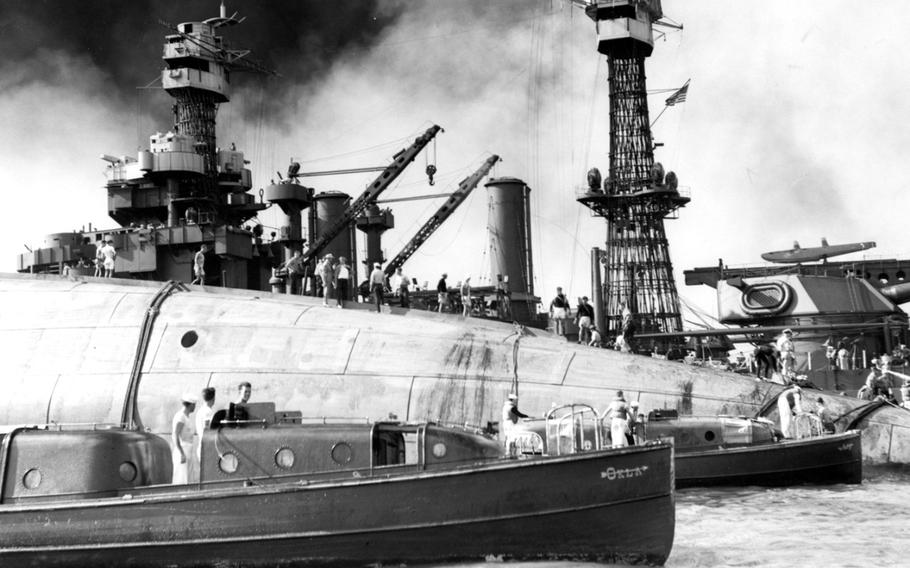 Rescue teams stand on the capsized hull of the USS Oklahoma on Dec. 7, 1941, in an attempt to save crew members trapped inside.
