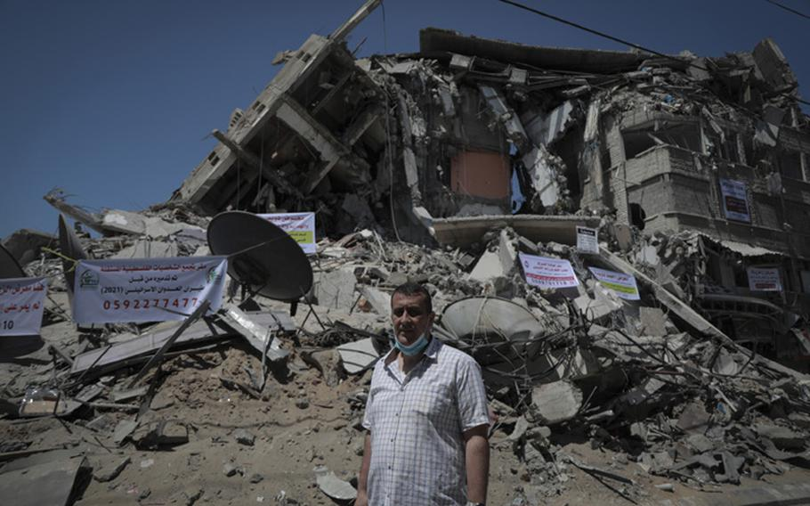 Naji Dwaima, owner of Dwaima's for Watches, stands on Sunday, May 23, 2021, in front of the rubble of a Gaza City building bombed by Israeli aircraft.