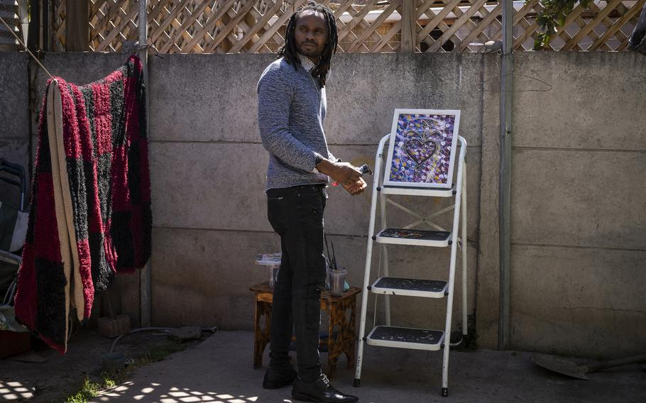 Emmanuel Louis paints in the backyard of his home in Quilicura.