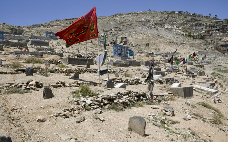 Flags fly over a cemetery in the Dasht-e-Barchi neighborhood, a majority Shiite district in the west part of Kabul, Afghanistan, where numerous funerals took place after an attack May 8, 2021, on a school there.