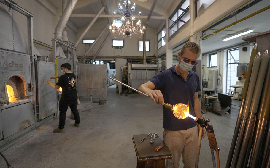 A glass-worker finishes a glass artistic creation in a factory in Murano island, Venice, Italy, Thursday, Oct. 7, 2021.