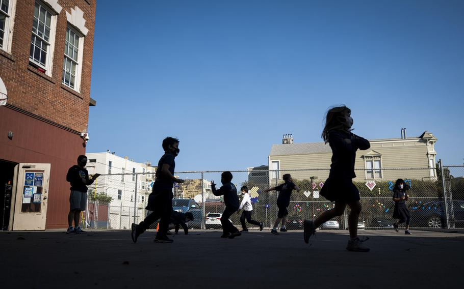 Students wearing protective masks exercise on the playground at an elementary school in San Francisco on Oct. 5, 2020.