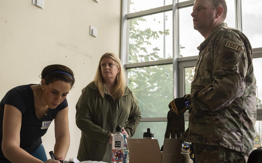 Heba Abdelaal, Heather Mecsko, and Master Sgt. Mitch Meis help organize a donation drive for Afghan refugees at Ramstein Air Base on Aug. 26, 2021.