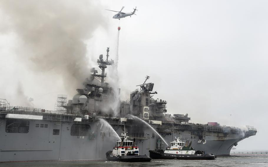 Federal firefighters and a helicopter from Helicopter Sea Combat Squadron 3 battle a blaze aboard the amphibious assault ship USS Bonhomme Richard at Naval Base San Diego, July 13, 2020.