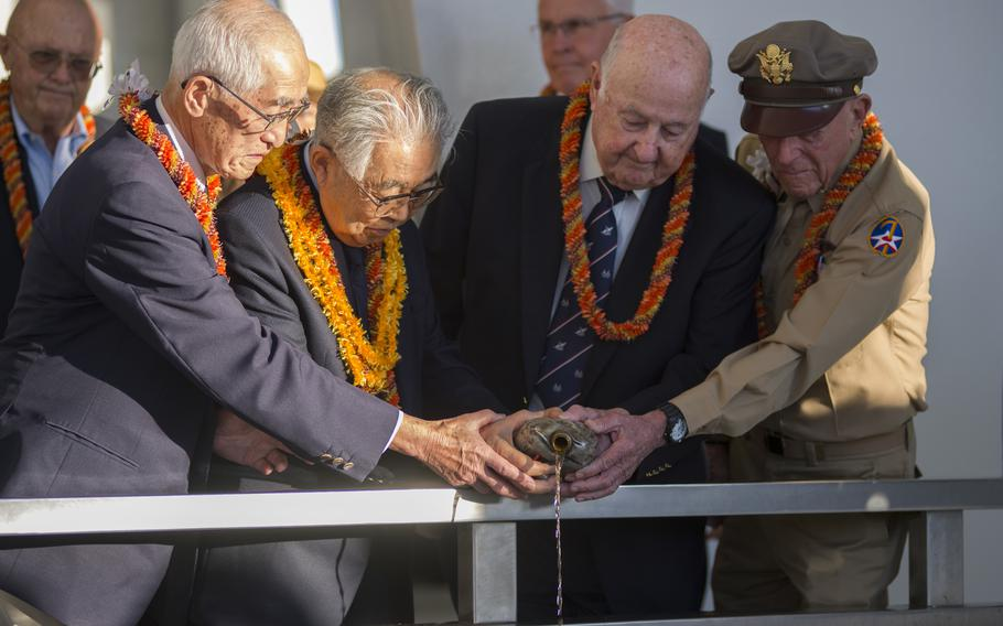 Shiro Wakita (left to right), former WWII Imperial Japanese Navy pilot; Dr. Hiroya Sugano, director general of the Zero Fighter Admirers Club; Jack Detour, former colonel and WWII Army Air Force B-25 pilot; Jerry Yellin, former captain and WWII Army Air Force P-51 pilot, pour bourbon whiskey at the sixth annual Blackened Canteen ceremony at the USS Arizona Memorial during the 75th Commemoration of the attacks on Pearl Harbor.