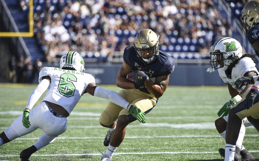 Navy wide receiver Jayden Umbarger runs the ball against Marshall defensive back Micah Abraham, left, during the first half of an NCAA college football game, Saturday, Sept. 4, 2021, in Annapolis, Md.