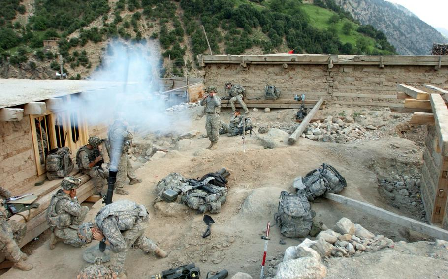 U.S. Army Soldiers with 1st Battalion, 32nd Infantry Regiment, 10th Mountain Division, fire mortar rounds at suspected Taliban fighting positions during Operation Mountain Fire, in the village of Barge Matal in eastern Nuristan province, Afghanistan in July 2009.