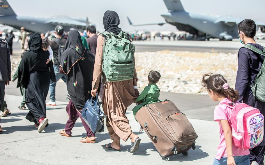 Afghan families walk toward their plane during an evacuation at Hamid Karzai International Airport in Kabul, Afghanistan, Tuesday, Aug. 24, 2021.