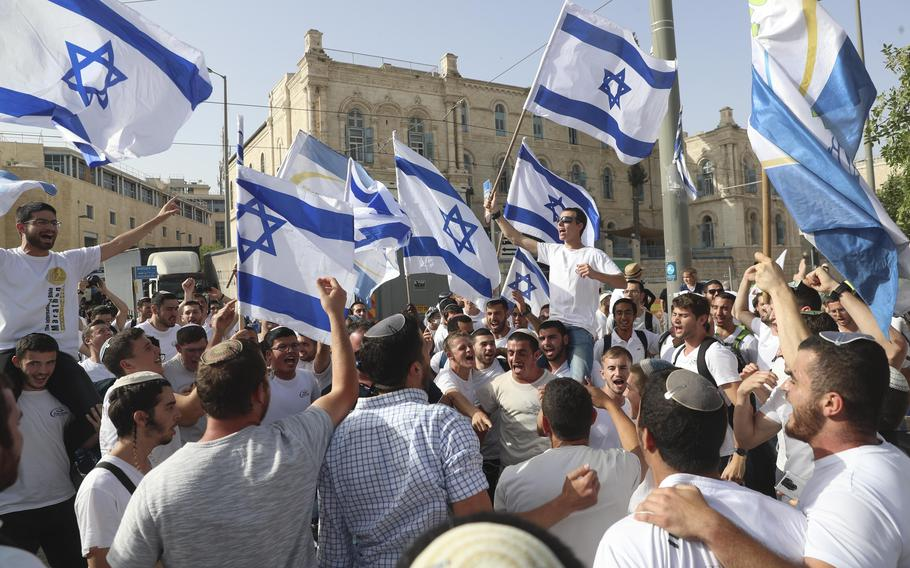 In this May 10, 2021, file photo, Israelis wave national flags during a Jerusalem Day parade, in Jerusalem.